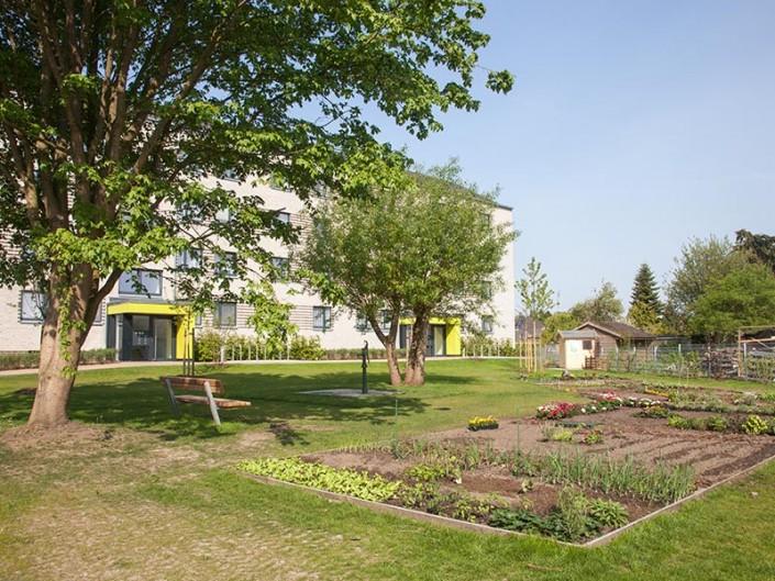 Gartengestaltung von Meykopff mit Beet und Brunnen in großer Wohnanlage