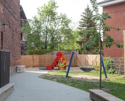 Spielplatzbau im Innenhof mit Pflasterarbeiten, Rutsche, Schaukel und Holz-Zaun