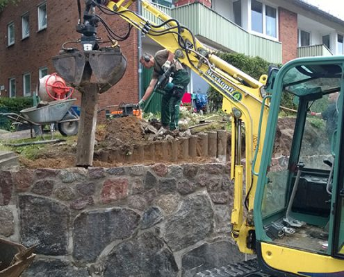 Meykopff Galabau Arbeiten an einer Natursteinmauer mit Bagger
