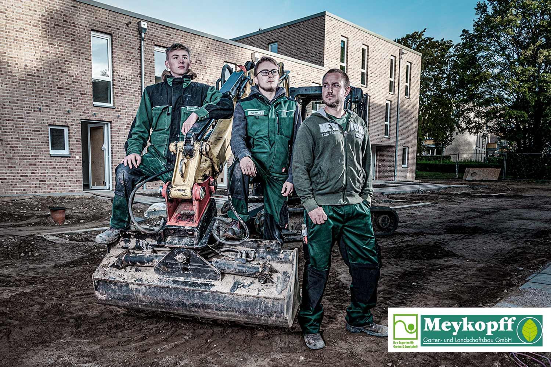 Meykopff-Luebeck-Garten-Landschaftsbau- Team sitzt vor dem Bagger