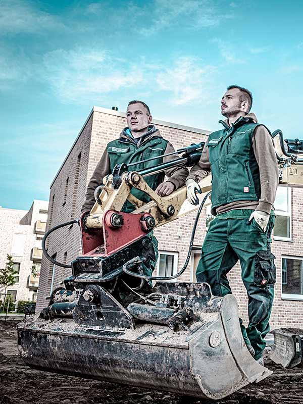 Meykopff-Luebeck-Garten-Landschaftsbau- Team stehen vor der Baggerschaufel